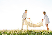 Young couple spreading picnic blanket on grass during sunny day