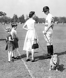 06/05/1956. Queen Elizabeth II holds one of the Royal corgis, while she speaks with the Duke of Edinburgh as he plays polo at Smith's Lawn, Windsor Great Park. The Royal couple will celebrate their platinum wedding anniversary on November 20.