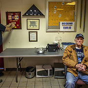 TAKOMA PARK, MD  - JAN 25: (L-R) Rich Fales, past commander of the Takoma Park VFW changes the date for an upcoming meeting at the post while Saturday afternoon card player Elmo Lewis relaxes at the VFW post in Takoma Park, Maryland, January 25, 2014. VFW Posts are dying all across the country but in the unlikely liberal haven of Takoma Park, the old VFW is showing signs of life. By throwing open the doors to private parties and concerts, the club is breaking even in spite of dwindling membership. Several times a month, the bar dwelling regular vets are sharing space with the bureaucrats, activists and peaceniks from the surrounding neighborhood. (Photo by Evelyn Hockstein/For The Washington Post)