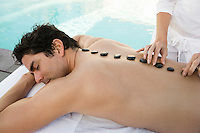 Man having stone therapy by swimming pool