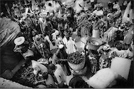 Thick crowd of Bozo residents gather before sun dried river fish on market day in Djenne, Mali, West Africa.  In the Sahel region of West Africa, river fish is a major source of protein and absolutely uninhospitable to large scale settlement without the Niger River system.