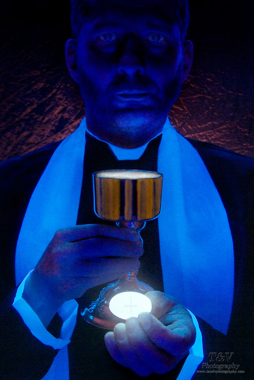 Priest with chalice and Eucharist.Black light