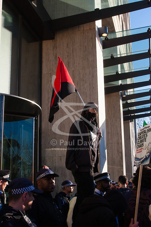 London, March 7th 2015. Following the Climate march through London, masked anarchists and environmental activists clash with police following a breakaway protest at Shell House. PICTURED: An anarchist stands on a ledge at Shell house, watched by  Met Police TSG officers.