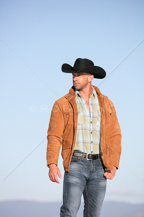 hot rugged cowboy in a suede jacket outdoors
