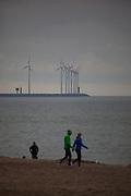 People on the beach at Knokke, Flanders, Belgium, with the wind turbines of Park Wind Farm in Zeebrugge behind.