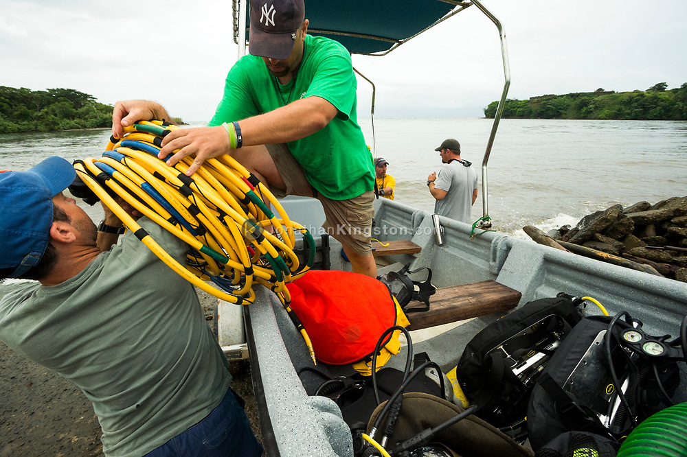 Men load yellow surface fed air supply hose into a boat in Panama. (Model Released)