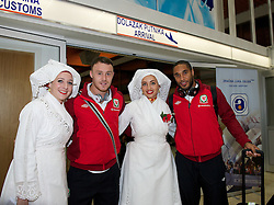 OSIJEK, CROATIA - Monday, October 15, 2012: Wales' Darcy Blake and captain Ashley Williams are greeted by girls in traditional Croatian costume as the team arrive at Osijek Airport ahead of the Brazil 2014 FIFA World Cup Qualifying Group A match against Croatia. (Pic by David Rawcliffe/Propaganda)
