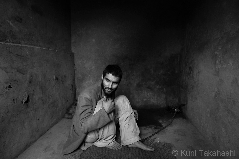 A mentally ill patient is chained in a cell at Mia Ali Saeb Shrine in Samar Khel, Afghanistan on Nov 12, 2008. Patients, usually brought here by family members, are only given daily rations of bread, black pepper and water, and are kept in their cells for 40 days. With mental illness widely misunderstood, many Afghans believe God will cure the patients with such treatment.