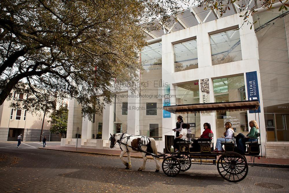 A horse drawn carriage passes the Telfair Museum in Savannah, Georgia, USA.