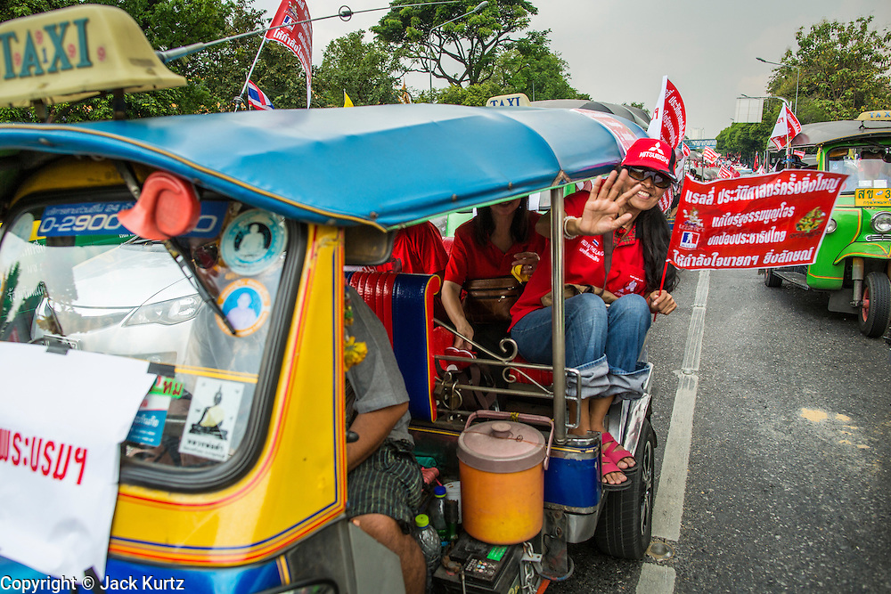 """10 DECEMBER 2012 - BANGKOK, THAILAND:   A convoy of Red Shirt """"tuk-tuks"""" (three wheeled taxis) go to the Pheu Thai offices on Petchaburi Road in Bangkok Monday. The Thai government announced on Monday, which is Constitution Day in Thailand, that will speed up its campaign to write a new charter. December 10 marks passage of the first permanent constitution in 1932 and Thailand's transition from an absolute monarchy to a constitutional monarchy. Several thousand """"Red Shirts,"""" supporters of ousted and exiled Prime Minister Thaksin Shinawatra, motorcaded through the city, stopping at government offices and the offices of the Pheu Thai ruling party to present demands for a new charter.       PHOTO BY JACK KURTZ"""