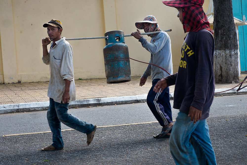 Workers transporting a gas bottle. Phnom Penh, Cambodia. <br />
