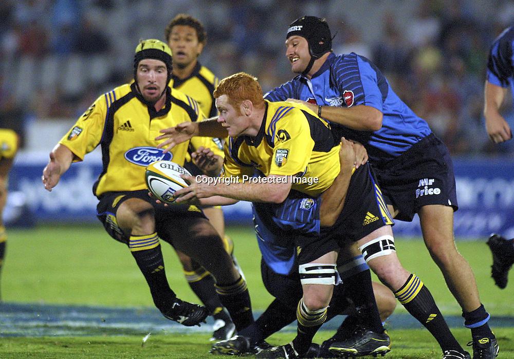 02/03/2002 Super 12 Bulls vs hurricanes at Loftus Versfeld Pretoria - Paul Tito  gets tagged by James Dalton and Chris le Roux (scrum cap).<br />Please credit: Photosport