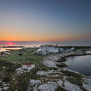 The sun rises over Cedar Island at the Isles of Shoals off Porstmouth, NH. The land in the front is part of Star Island, with the historic Oceanic hotel at center.