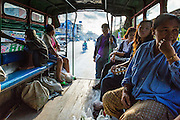 30 APRIL 2013 - MAHACHAI, SAMUT SAKHON, THAILAND:   Passengers on a truck converted to use as a bus in Mahachai, Samut Sakhon province, Thailand. Pickup trucks are frequently converted to use as buses by the installation of bench seats in the back. Called songthaews, they are common sight in Thailand. Conversion of large trucks is less common but happens in large towns with a large population of factory workers. Samut Sakhon has a very large population of Burmese migrant workers who work in the fishing industry and electronics factories in town.         PHOTO BY JACK KURTZ