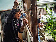 06 OCTOBER 2016 - BANGKOK, THAILAND:  A demolition worker takes apart the slatted window of a home workers dismantled in Pom Mahakan. Evictions are continuing at a slow pace in Pom Mahakan Fort and as people move out their homes are destroyed to ensure new squatters don't move in. More than 40 families still live in the Pom Mahakan Fort community. Bangkok officials are trying to move them out of the fort and community leaders are barricading themselves in the fort. The residents of the historic fort are joined almost every day by community activists from around Bangkok who support their efforts to stay. City officials said recently that they expect to have the old fort cleared of residents and construction on the new park started by the end of 2016.     PHOTO BY JACK KURTZ