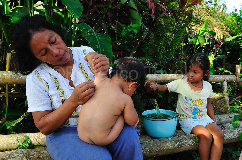 Flora Mamallacta giving a medical herbs bath to this son that suffering a bronchial disease