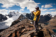 Trekking guide, Luis Mamani, plays his quena (an andean flute) with Mt. Condoriri (18,525 ft / 5648 m) in the background from the summit of Pico Austria (17,385 ft / 5300 m) in Bolivia's Cordillera Real during typical winter weather.