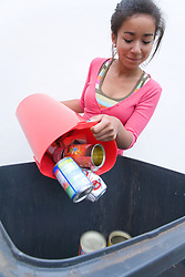 Teenage girl putting tins and cans into recycling wheelie bin ready for collection,