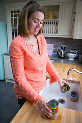 Woman rinsing out tins at kitchen sink before putting out for recycling,