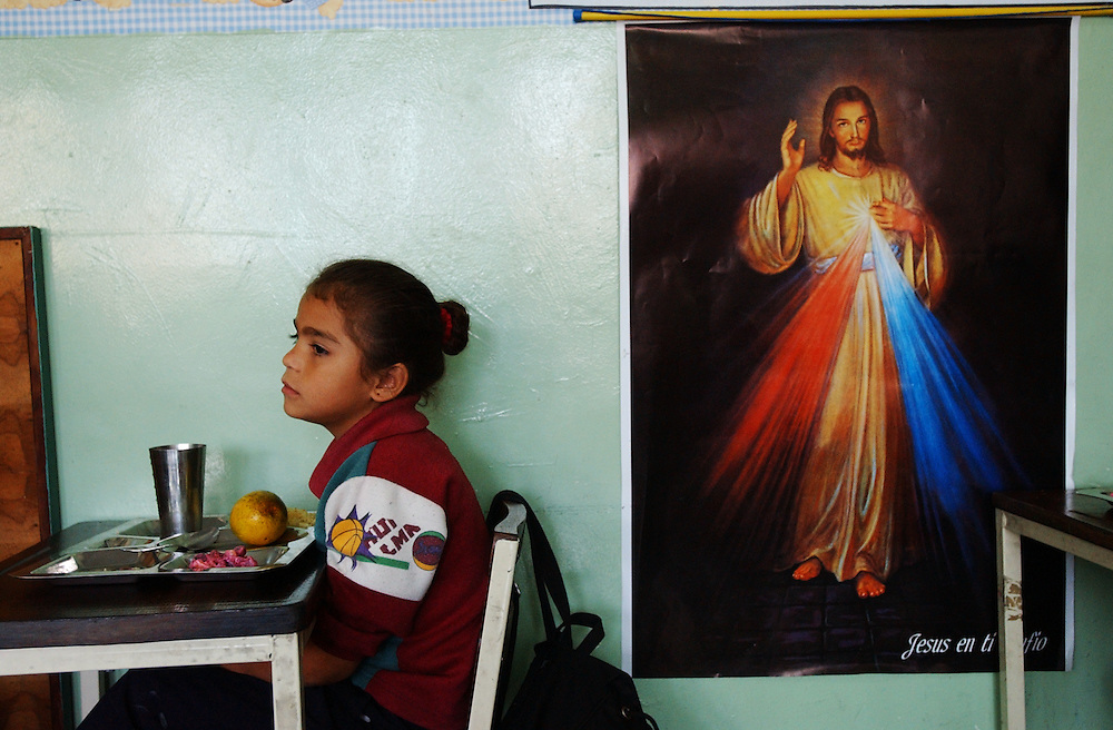 "Scarleth Pérez waits to say grace before eating lunchin her first grade classroom at the Florencio Jimenez school.  The school is one of the new ""Bolivarian"" Schools which are part of President Chavez's Education Reform.  The new Bolivarian Schools keep students for an entire day, as opposed to a half day, feed the students lunch and offer programs like drama, art and music. While President Chavez touts his programs that benefit the poor, many point to a rising poverty rate and shrinking economy and claim the programs fail to substantially help."