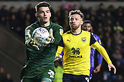 Shrewsbury Town defender goalkeeper (on loan from Bristol City) Max O'Leary (25) catches under pressure  from Oxford United forward (on loan from Bristol City) Matty Taylor (9) during the EFL Sky Bet League 1 match between Oxford United and Shrewsbury Town at the Kassam Stadium, Oxford, England on 7 December 2019.