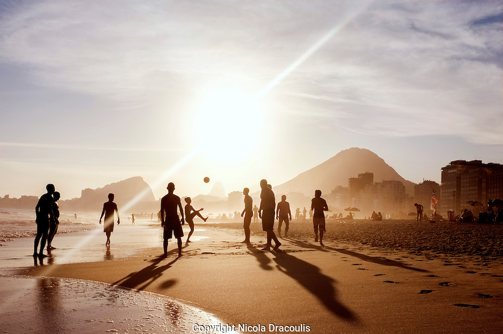 A group of guys play altinho at Copacabana Beach. Altinho is a popular beach football game in Brazil.