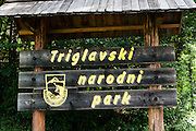 "Triglavski narodni park (TNP) sign, Slovenia. Tolmin gorges (Tolminska korita) are among the longest and deepest gorges in Slovenia and are the lowest point (180 meters elevation) in Triglav National Park (TNP). Walk a trail to the confluence of two gorges (Tolminka and Zadlascica rivers), then along Zadlascica river canyon (locally called Skakalce, ""the jumps"") up to a chock stone called the ""Bear's Head"" (Medvedova glava). Walk onwards to the scenic Devil's Bridge (Hudicev most, built 1907), which carries Tolmin-Cadrg road sixty meters above Tolminka River, then walk the loop back to the parking lot at the Triglavski narodni park (TNP) sign, near Zatolmin, Slovenia, Europe. (The Slovene letters sc in Zadla??ica may not display in some media.)"