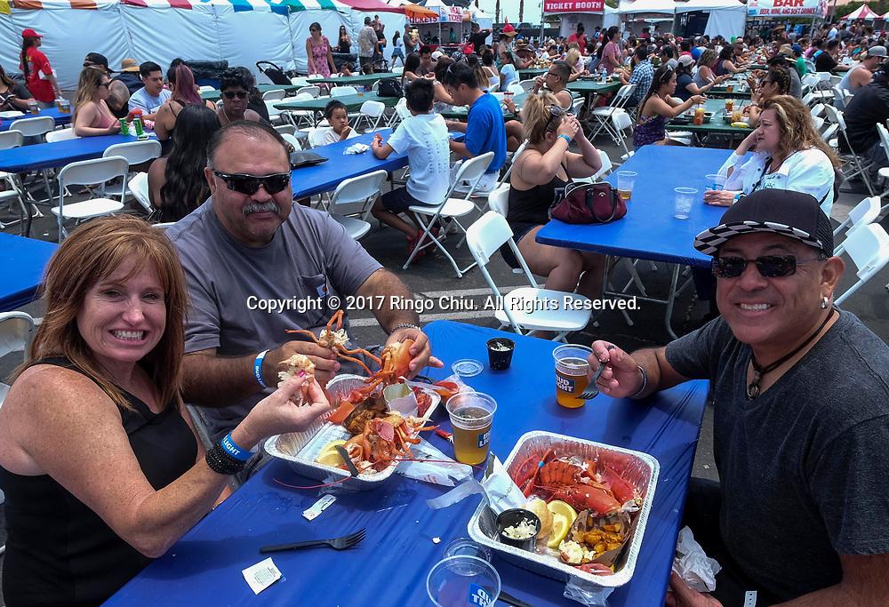 新华社照片,洛杉矶,2017年7月17日<br />     (国际)(1)第十九届年度洛杉矶港口龙虾节<br />     7月16日,民众品尝新鲜龙虾大餐。<br />     在美国洛杉矶圣佩德罗,大批民众出席了号称世界上最大龙虾节&quot;第十九届年度洛杉矶港口龙虾节&quot;。<br />     新华社发(赵汉荣摄)<br /> People enjoy the lobsters at the 19th Annual Port of Los Angeles Lobster Festival in San Pedro, California, the United States, Sunday, July 16, 2017. The world&rsquo;s largest lobster festival, which has been a Southern California tradition since 1999. The event features fresh Maine lobster, wine and draft beer, free entertainment, live music, shopping, and other culinary delights. (Xinhua/Zhao Hanrong)(Photo by Ringo Chiu)<br /> <br /> Usage Notes: This content is intended for editorial use only. For other uses, additional clearances may be required.