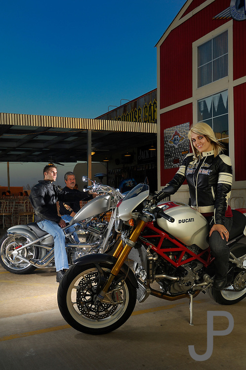 Emily Murray on Ducati Monster in front of OKC Thunder Cycles cafe with guys on bikes watching.