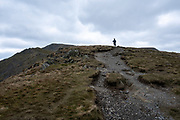 A hiker stands alone on the rugged footpath leading up Blencathra Fell in Lake District National Park, Cumbria, UK. The hill is also known as Saddleback and is one of the most northerly hills in the Lake District. The sky is full of clouds. (photo by Andrew Aitchison / In pictures via Getty Images)