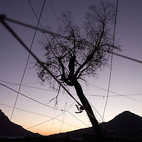 A man illegally joins electric cable above shacks in Imizamo Yethu, Hout Bay, Cape Town, South Africa. The work of the CPF and neighbourhood watch have seen the crime rate in Hout Bay drop 63%, but relations between the shanty town of Imizamo Yethu and Hout Bay are tense.  photo  Leonie Marinovich