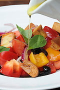 Mediterranean Salad - Olive oil is poured on a freshly cut salad of Tomato, bell peppers, onions and black olives