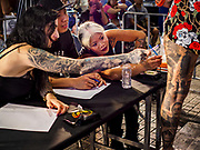 28 OCTOBER 2018 - BANGKOK, THAILAND: Judges score a woman's tattooed leg during judging of the Realistic division at the 2018 MBK Center Tattoo Fest. Tatoo artists from around the world came to participate in the festival, which featured both modern (using tattoo machines) and traditional methods (done by hand with long needles) of tattooing.     PHOTO BY JACK KURTZ