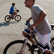 September 9, 2012 - Brooklyn, NY : Once New York City's municipal airport, Floyd Bennett Field is now administered by the Parks Department as a recreation site. The old runways remain -- providing ideal space to ride bikes and fly model airplanes.  Pictured here, Dante Lopez, foreground, and his five-year-old son Carlos ride bicycles on Sunday afternoon. Dante expressed that Floyd Bennett Field, with its wide open spaces devoid of vehicular traffic, is the ideal place for inexperienced riders like Carlos, who just learned to ride his bicycle two weeks ago. CREDIT: Karsten Moran for The New York Times