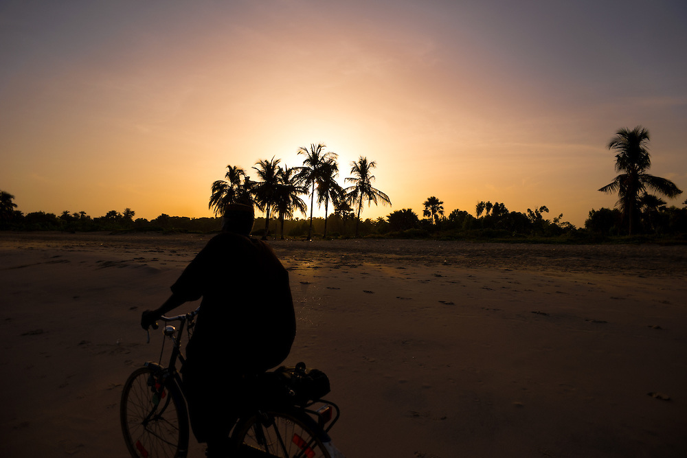 Man riding his bicycle on the beach at sunrise, Kololi, The Gambia.