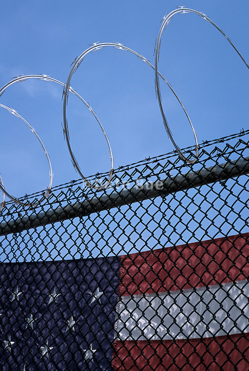 American flag behind fence with razor wire