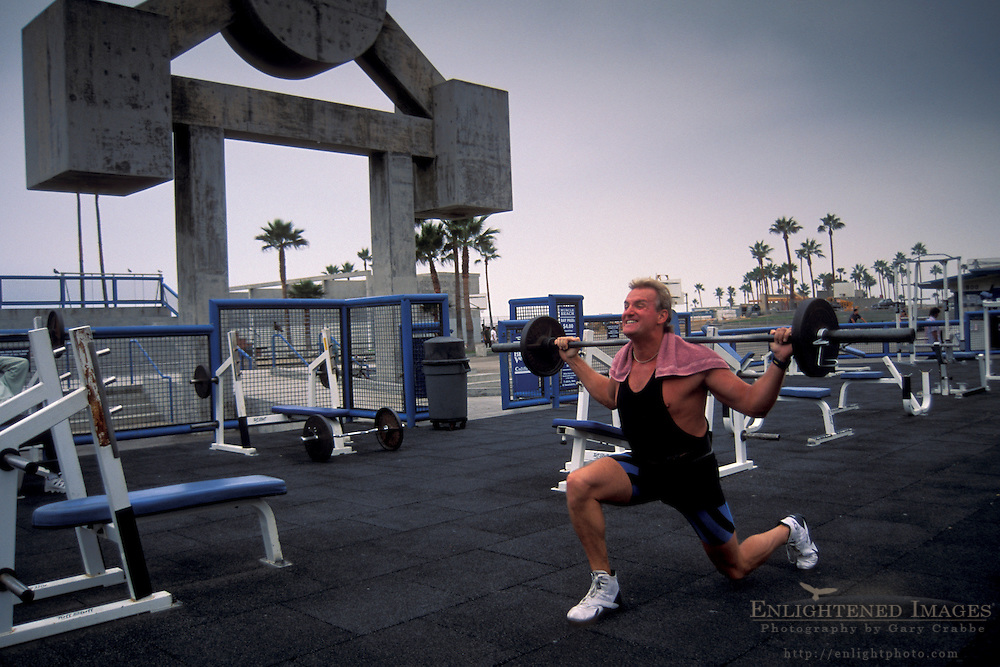 Athletic man working out lifting weight barbell at outdoor gym, Muscle Beach, Venice Beach, Santa Monica, California