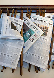 Newspapers hanging on rack at famous Cafe Einstein in Charlottenburg in Berlin Germany