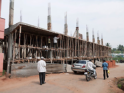 Building site featuring wooden scaffolding tied with rope, Mysore