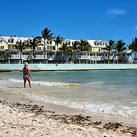 Woman Wading at South Beach in Key West, Florida<br /> Key West's South Beach will never be mistaken for the famous one in Miami Beach.  This cube of sand measures only 200 feet and practically disappears at high tide. But it is popular among tourists and locals, just as it was for playwright Tennessee Williams when he visited his Key West home between 1949 and 1983.  It is located at the end of Duvall Street next to the South Beach Pier.