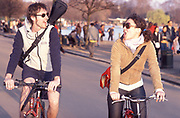 A man and woman, on bicycles, riding through a park, London, UK 2004
