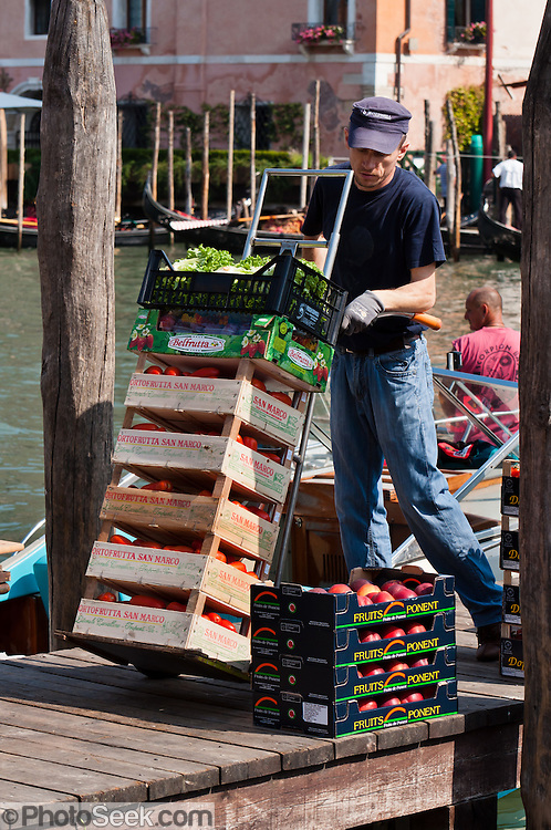 "A market vender offloads fresh fruit by boat. Venice (Venezia) is the capital of Italy's Veneto region, named for the ancient Veneti people from the 10th century BC. The romantic ""City of Canals"" stretches across 117 small islands in the marshy Venetian Lagoon along the Adriatic Sea in northeast Italy, between the mouths of the Po (south) and Piave (north) Rivers. The Republic of Venice was a major maritime power during the Middle Ages and Renaissance, a staging area for the Crusades, and a major center of art and commerce (silk, grain and spice trade) from the 13th through 17th centuries. The wealthy legacy of Venice stands today in a rich architecture combining Gothic, Byzantine, and Arab styles. Composer Antonio Vivaldi (1678-1741) was born in Venice."