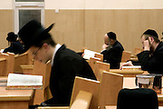 Orthodox Jewish men  during Morning Prayer inside a Stamford Hill synagogue. Communal praying in a minyan (quorum) is preferred by men who wear a Tallit (prayer shawl) and a Tefillin (a box containing strips of parchment inscribed with 4 passages of the Torah) on their heads with the leather straps around their arm and hand.