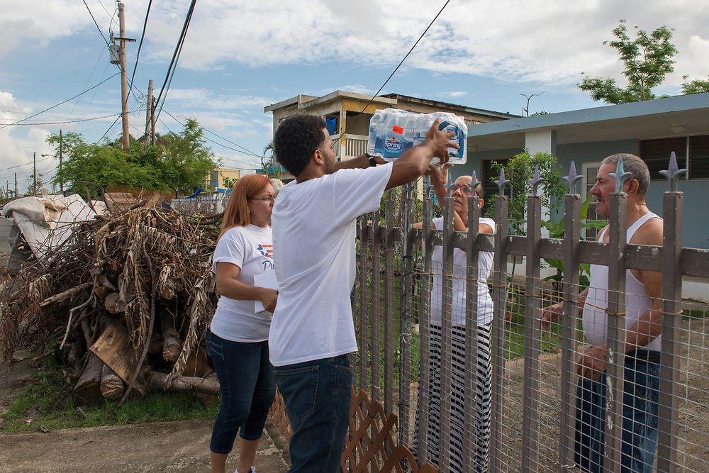 Toa Baja, PR, November 10, 2017--Inamarys Carreras and Yoba D. Medina are part of a team of faculty and staff of Escuela Delia Cabán who continue to distribute water and emergency relief in Tao Baja, PR neighborhoods still without power and water 50 days after Hurricane Maria.  Escuela Delia Cabán has served as a distribution point for the Puerto Rico Recovery Fund's emergency relief efforts since it was established days after the storm hit September 20, 2017.  Photo by Lori Waselchuk/BRAF
