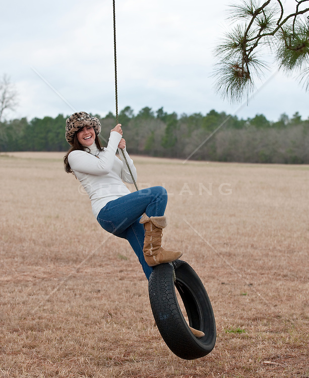 Young woman in a fur hat standing while swinging on a tire swing