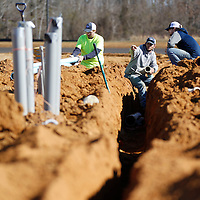 Thomas Wells | BUY AT PHOTOS.DJOURNAL.COM<br /> Chris Taylor, from left, Hunter Highfield and Tyler Dowdy assemble and install the main water line that will feed the new five baseball fields under construction in Corinth.