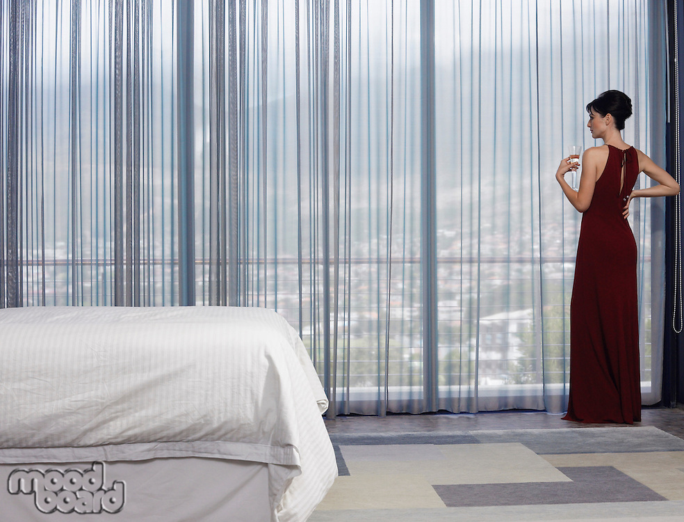 Woman wearing elegant dress looking out of window in bedroom