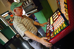 Man playing on a fruit machine in a pub,