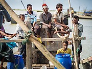 07 NOVEMBER 2014 - SITTWE, RAKHINE, MYANMAR: Rohingya Muslim fishermen on a boat in the port of a Rohingya IDP camp near Sittwe. After sectarian violence devastated Rohingya communities and left hundreds of Rohingya dead in 2012, the government of Myanmar forced more than 140,000 Rohingya Muslims who used to live in and around Sittwe, Myanmar, into squalid Internal Displaced Persons camps. The government says the Rohingya are not Burmese citizens, that they are illegal immigrants from Bangladesh. The Bangladesh government says the Rohingya are Burmese and the Rohingya insist that they have lived in Burma for generations. The camps are about 20 minutes from Sittwe but the Rohingya who live in the camps are not allowed to leave without government permission. They are not allowed to work outside the camps, they are not allowed to go to Sittwe to use the hospital, go to school or do business. The camps have no electricity. Water is delivered through community wells. There are small schools funded by NOGs in the camps and a few private clinics but medical care is costly and not reliable.   PHOTO BY JACK KURTZ