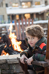 little boy sitting by a fire pit at a ski lodge
